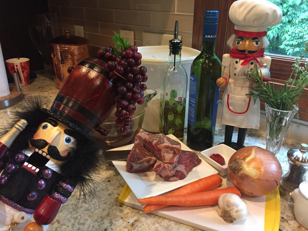 Short ribs, carrots, onion, garlic tomato paste on a cutting board With a nutcracker that looks like a chef and another nutcracker that looks like a sommelier