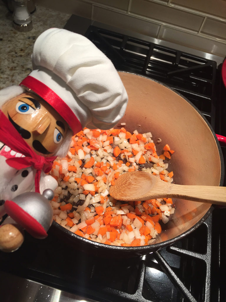 chopped carrots and onions in a dutch oven and stirred with a wooden spoon. There's a nutcracker that looks like a chef in the foreground.