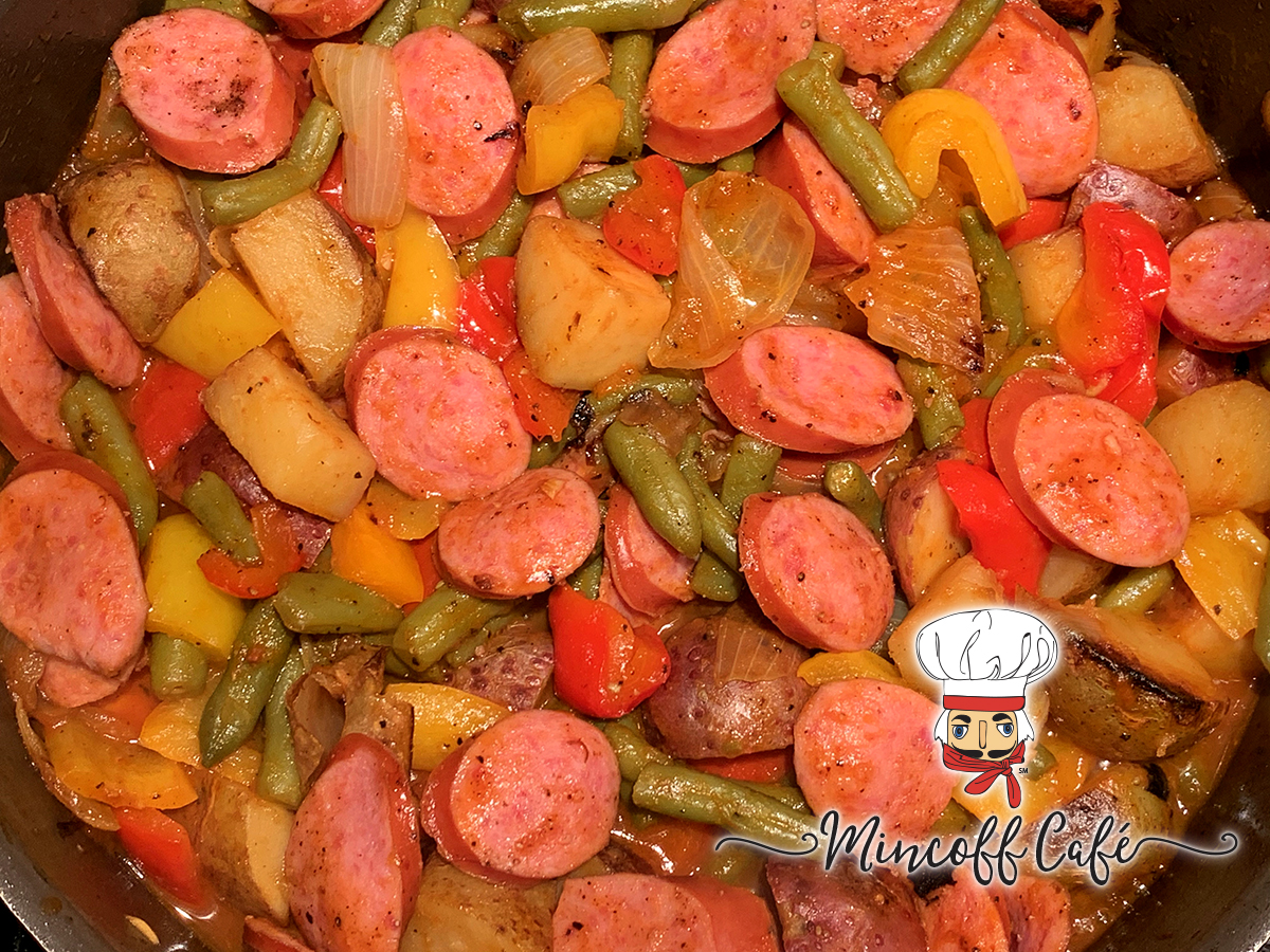 Skillet filled with sliced smoked sausage, onions, red and yellow bell peppers and green beans. There's a nutcracker in the foreground who looks like a chef.