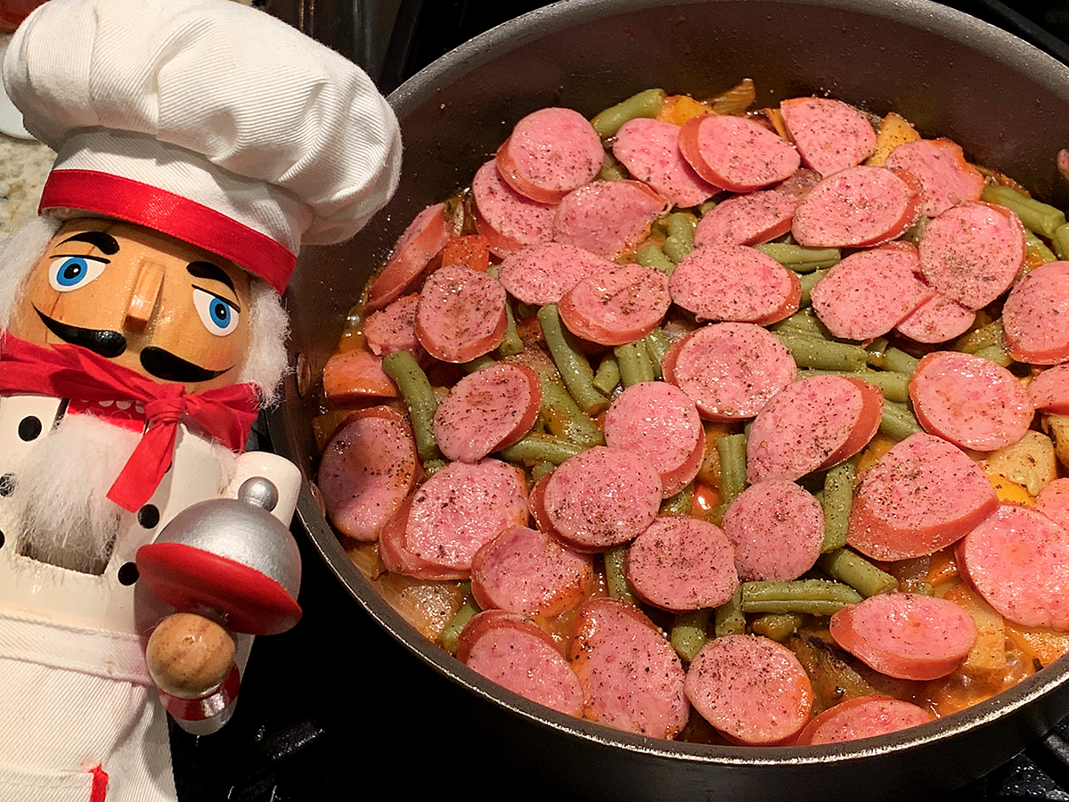 Skillet with green beans, pepper and potatoes with a layers of sliced polish sausage on top. There's a nutcracker in the foreground who looks like a chef.