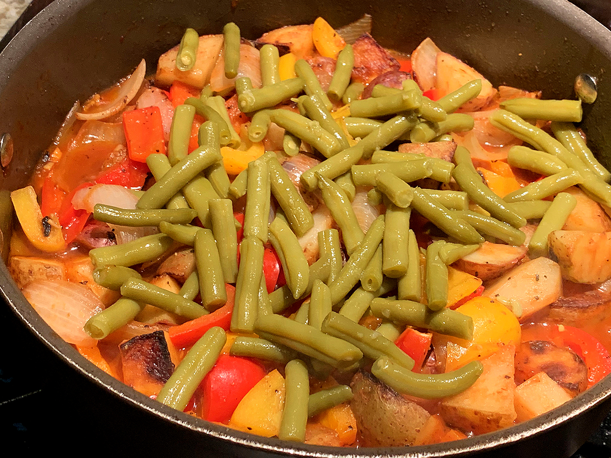 Skillet filled with, onions, red and yellow bell peppers and green beans.