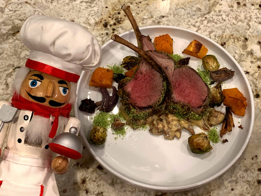 Two medium rare herb crusted racks of lamb with a chanterelle cream sauce on a round white plate with roasted butternut squash, brussels sprouts and red onions. All on a white round plate and with nutcracker who looks like a chef in the foreground.