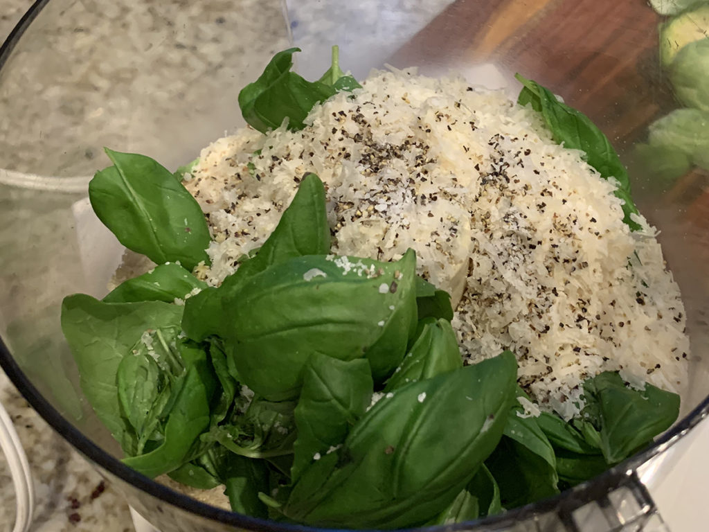 Fresh basil, panko bread crumbs, parmesan cheese, salt & pepper ready to be blended in a food processor.