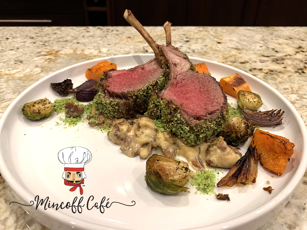 Two medium rare herb crusted racks of lamb with a chanterelle cream sauce on a round white plate with roasted butternut squash, brussels sprouts and red onions.