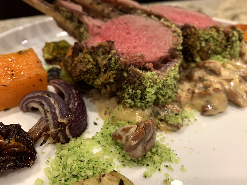 Close up image of medium rare herb crusted rack of lamb with roasted veggies and a chanterelle cream sauce.