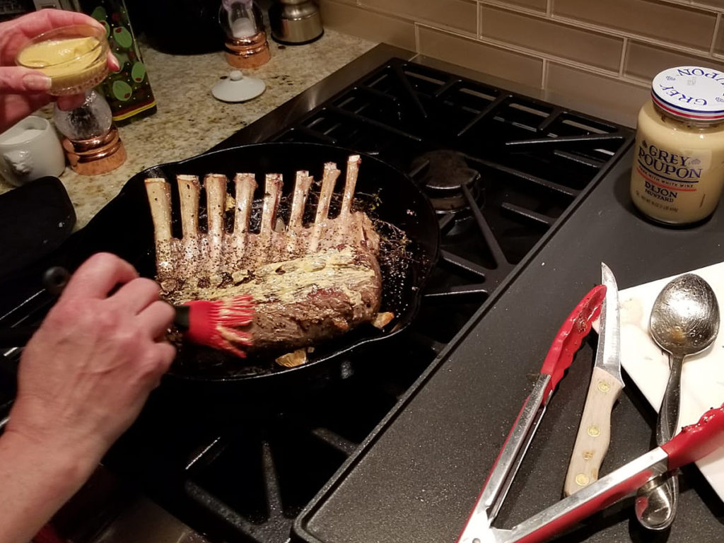 Seared rack of lamb in iron skillet getting brushed with dijon mustard.
