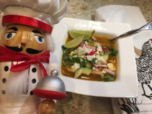 Chicken Posolé soup garnished with limes, red radishes, avocados, jalapeños and cilantro in a white square bowl. There's a nutcracker who looks like a chef in the foreground to the left.