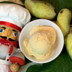 Pale orange scoop of ice cream in a small round white bowl, surrounded by fresh whole pale green pawpaws and pawpaw leaves, and a nutcracker who looks like a chef.