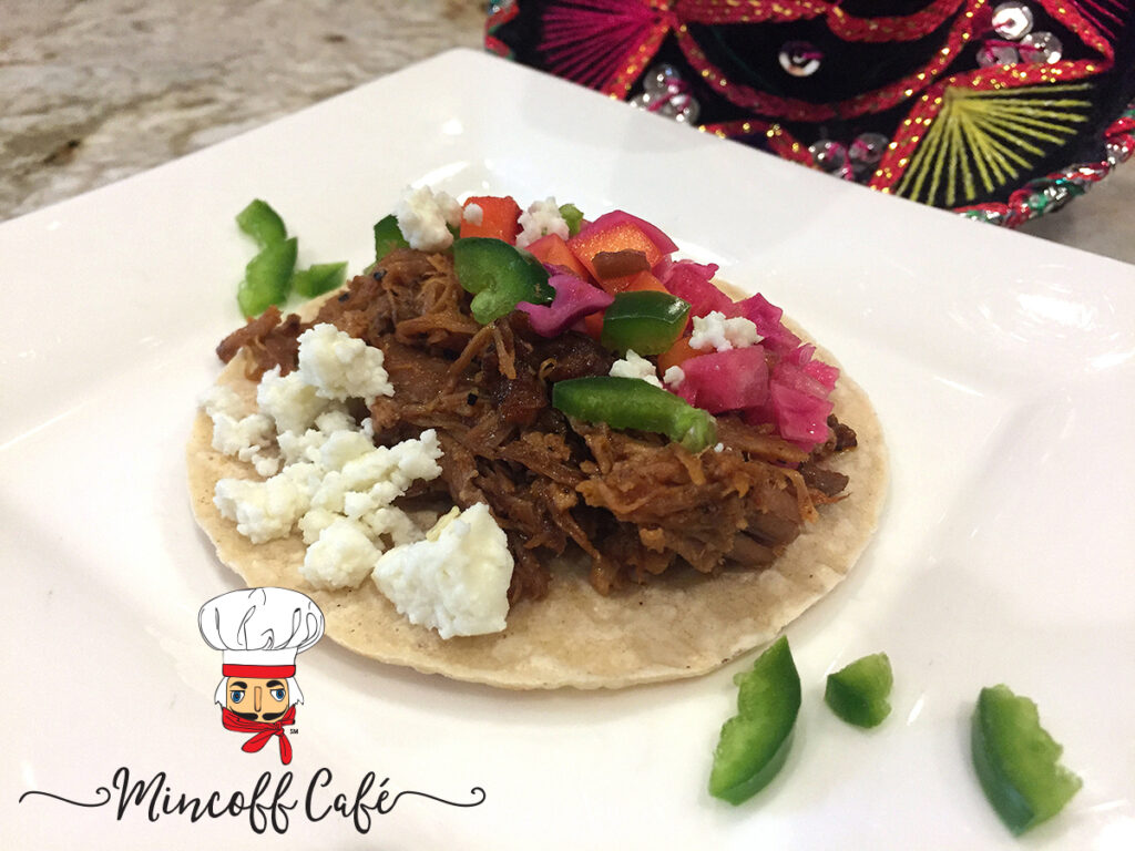 Pulled pork, jicama mango slaw, white cheese and chopped green jalapenos on a small corn tortilla, which is a street taco on a white plate.
