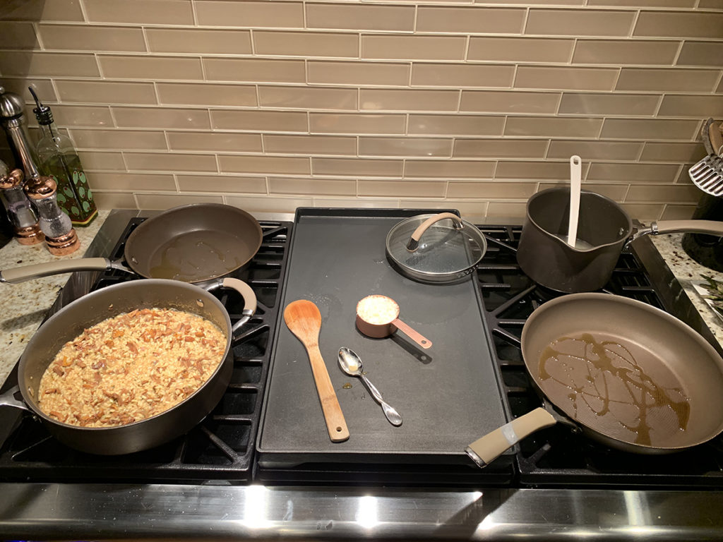 stovetop with risotto in one skillet, a drizzle of olive oil in two more skillets, chicken stock in a sauce pan with a large griddle between the four burners.