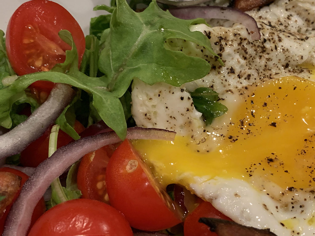 Close up image of cherry tomatoes, red onion slices, arugula and a fried egg with a runny yolk. egg is cut to show runny yolk.