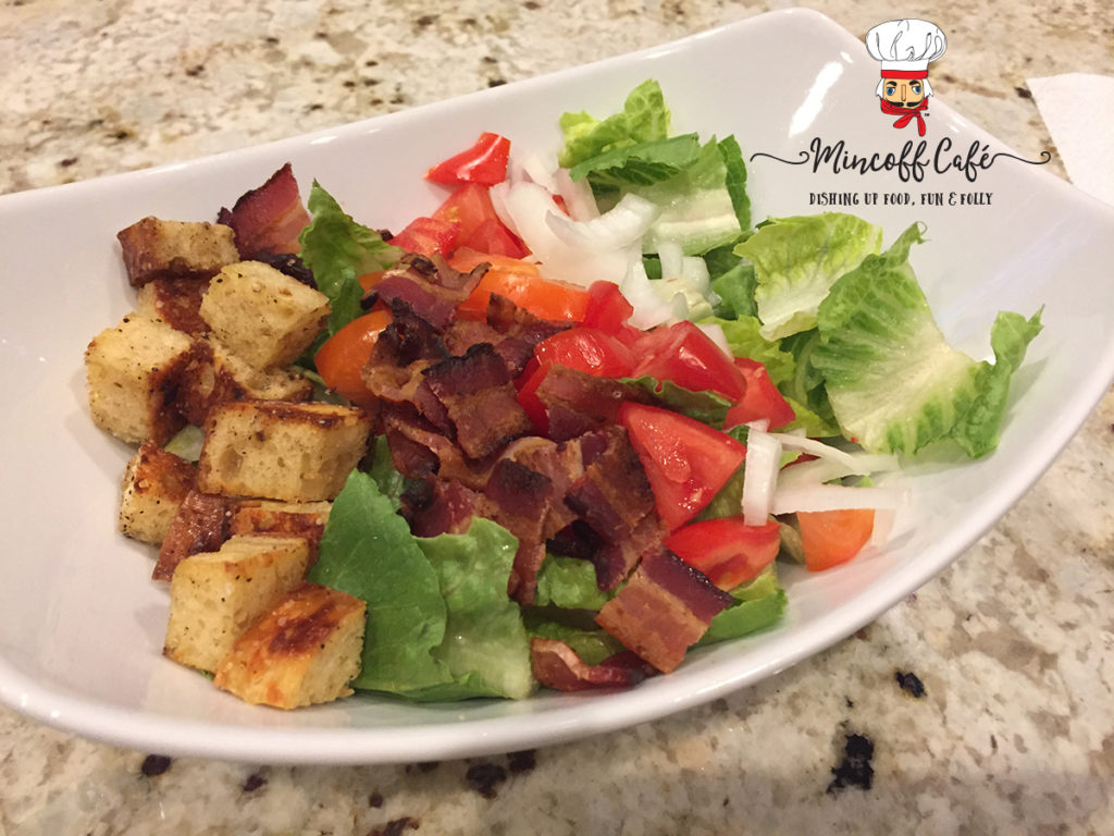 Bacon, lettuce, tomato, onions and croutons in a white bowl