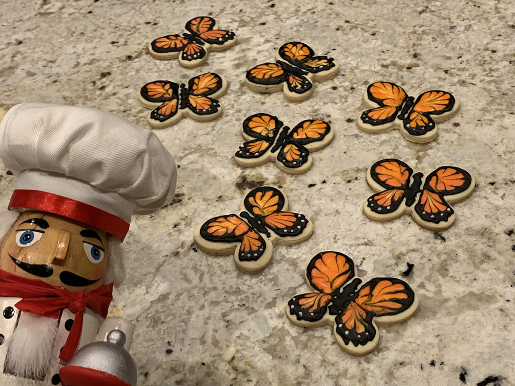 Eight sugar cookies decorated to look like monarch butterflies and a nutcracker who looks like a chef. All on a granite countertop.