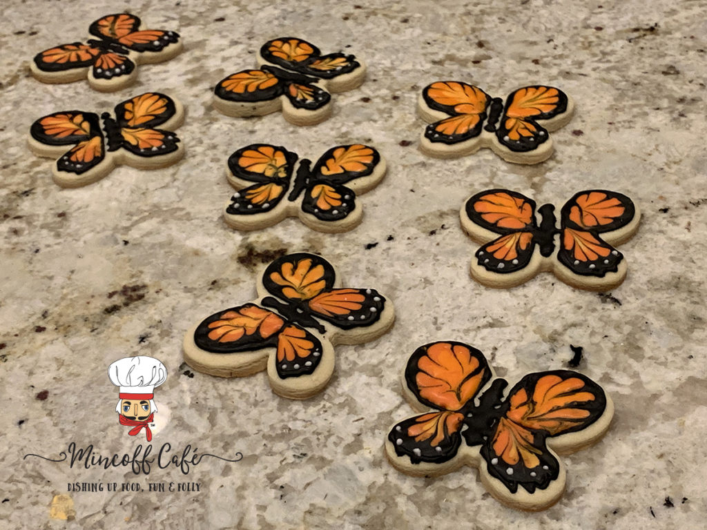 Eight sugar cookies decorated to look like monarch butterflies on a granite countertop.