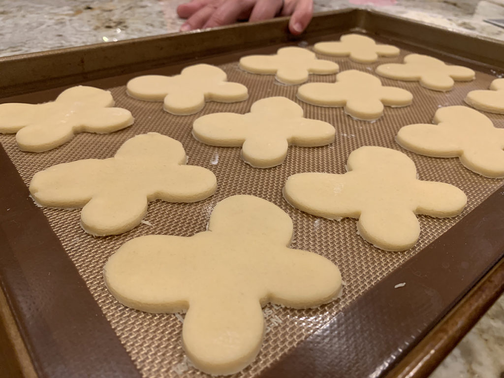 Raw butterfly cookies on a cookie sheet lines with a silicone mat.