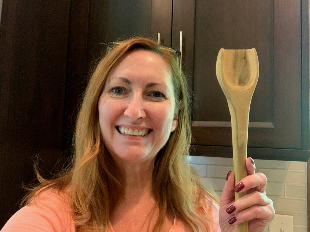 Happy caucasian woman with red hair holding a flat bottomed wooden spoon up to display.