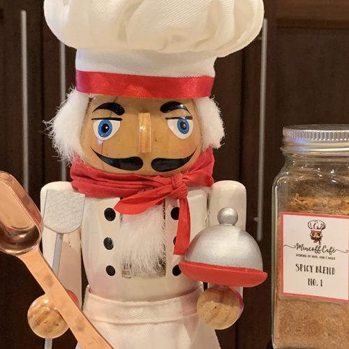 spice blend of oregano, garlic powder, cumin & cayenne pepper in a jar next to a nutcracker that looks like a chef. He's holding a copper measuring spoon.