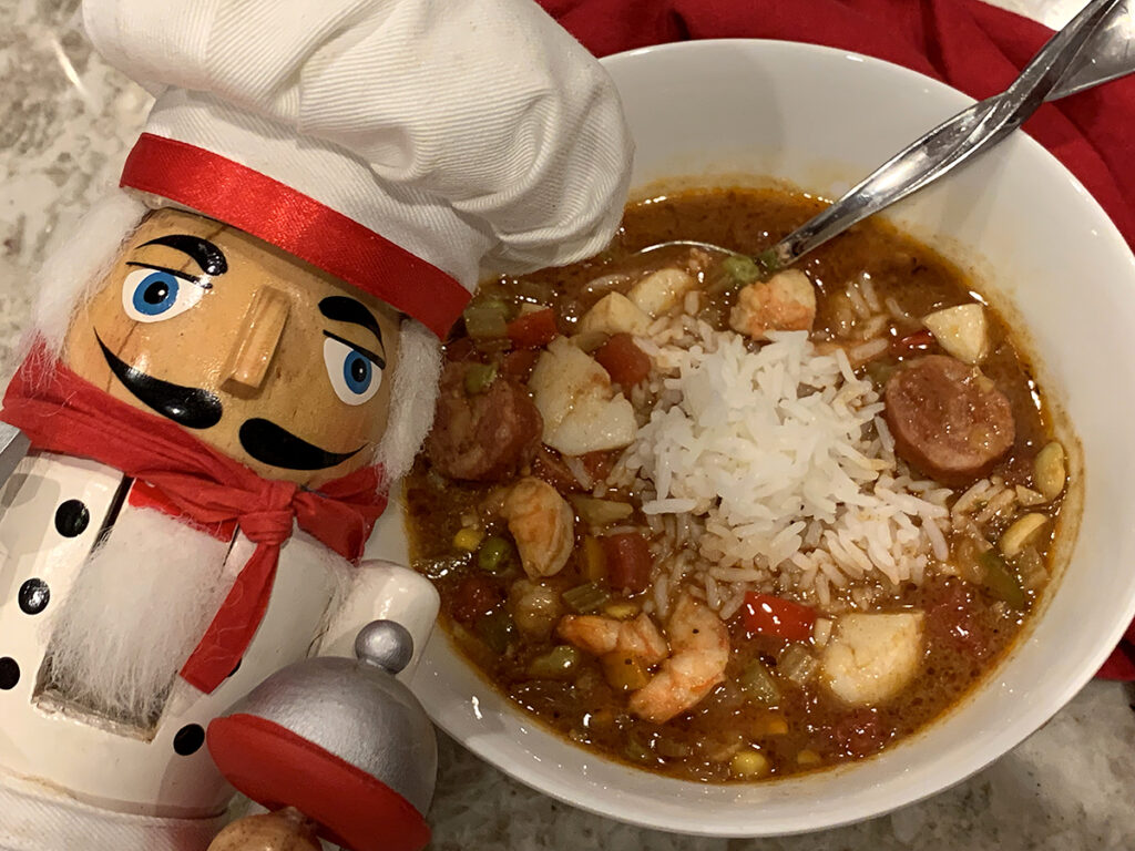 seafood & chicken gumbo in a white bowl on a tan granite countertop with a nutcracker that looks like a chef
