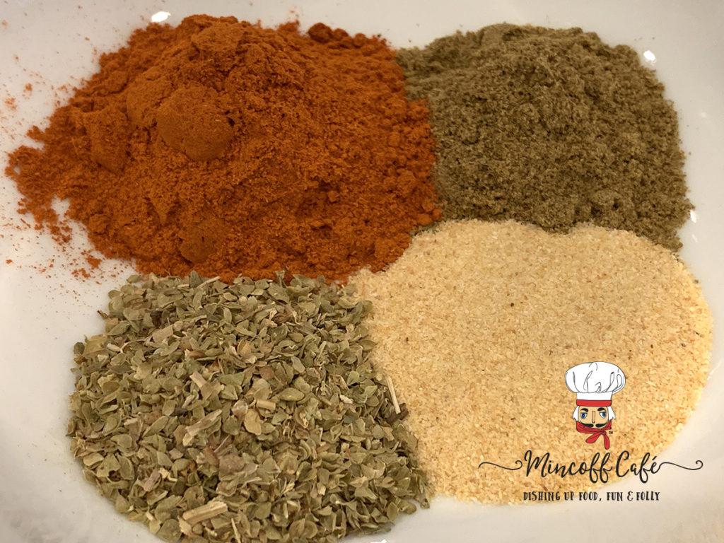 Oregano, garlic powder, cumin & cayenne pepper in small piles in a white bowl. Mincoff Cafe logo in foreground.
