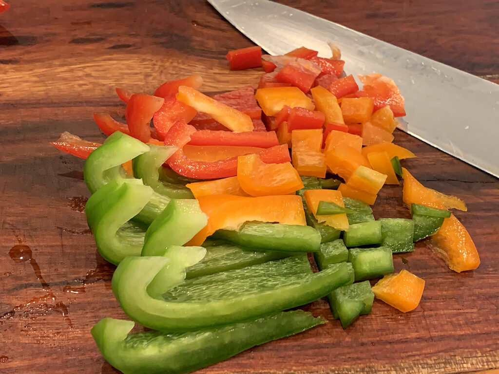 Green, red and orange bell peppers partially chopped on a wooden board with a chef knife.