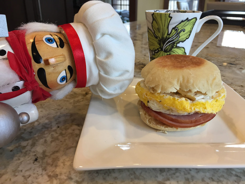 Breakfast sandwich made with egg, Canadian bacon and brie cheese, sitting on a square white plate. Nutcracker who looks like a chef to the left and a white tea cup with an illustration of a green leaf on it.