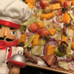 chunks of roasted fall veggies (butternut squash, brussels sprouts, red beets, fennel bulbs and red onions) on a sheet pan with a nutcracker that looks like a chef in the foreground..