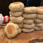 16 homemade English muffins stacked in 3 columns with one in front. All on a wood board with a nutcracker who looks like a chef laying on his side peeking out behind them.