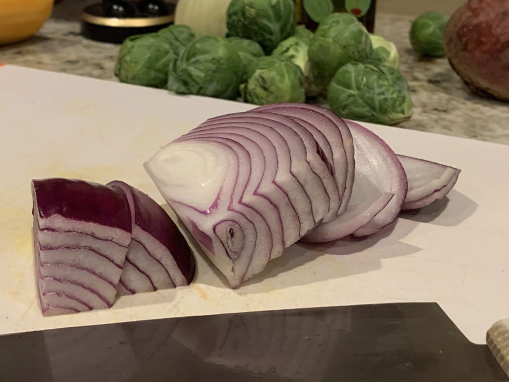 large chunks of red onions on a white cutting board with a chef knife in the foreground and some uncut brussles sprouts in the background.