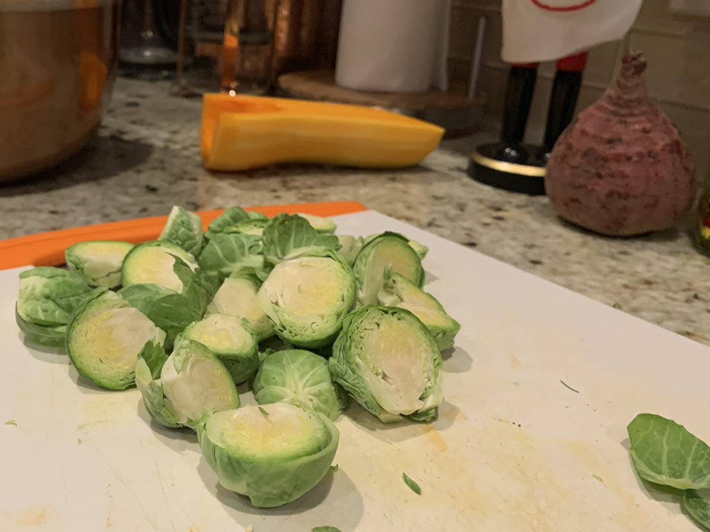 a small pile of Brussels sprouts cut into halves on a white cutting board. Half of a butternut squash and a beet root in the background.