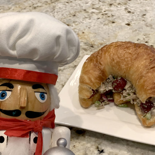 Turkey salad sandwich with turkey, celery, red grapes and onions on a croissant, sitting on a white square plate. There's a nutcracker that looks like a chef in the foreground to the left.