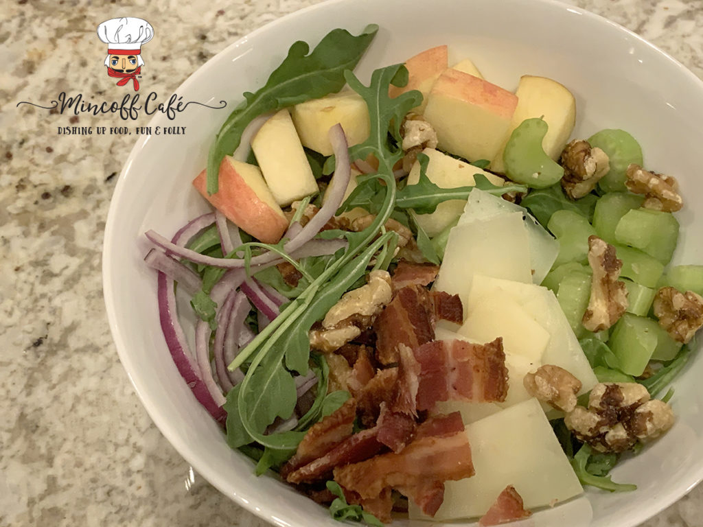Bacon, Apple, celery, red onions, walnuts, manchego cheese and arugala salad in a while bowl