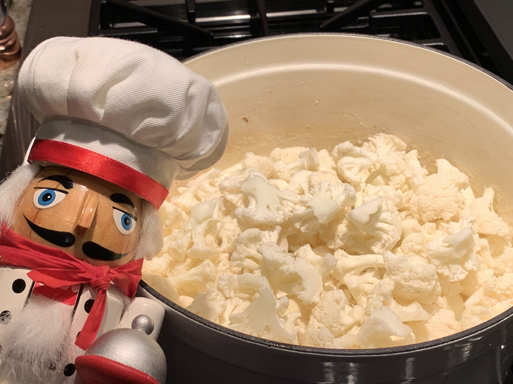 Chunks of cauliflower added to a white dutch oven with a nutcracker who looks life a chef in the foreground on the left.