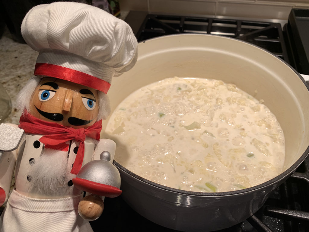 Pepé the nutcracker next to his very pale yellow cauliflower soup in a white dutch oven, still on the stove.
