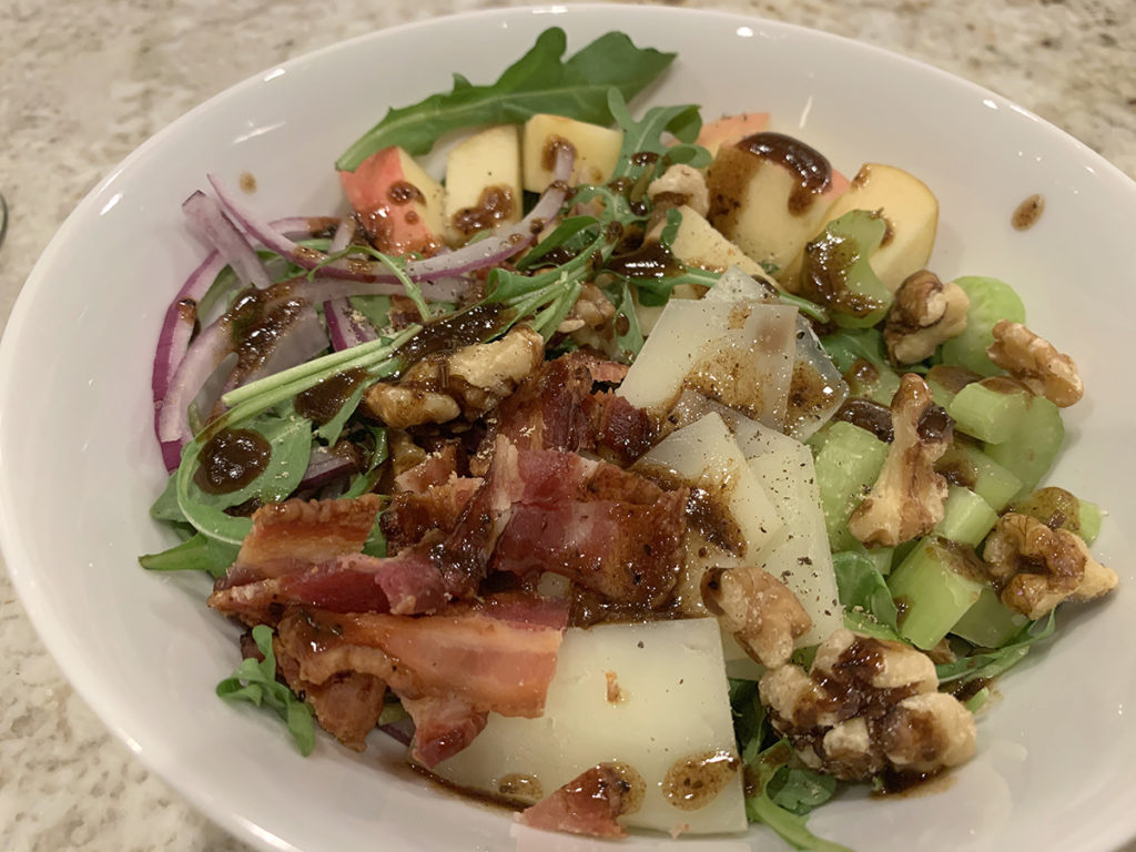 Bacon, Apple, celery, red onions, walnuts, manchego cheese and arugula salad in a while bowl. Topped with a balsamic vinaigrette.