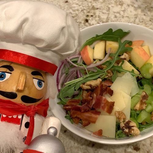 Bacon, Apple, celery, red onions, walnuts, manchego cheese and arugala salad in a while bowl, with a nutcracker who looks like a chef in the foreground on the left.