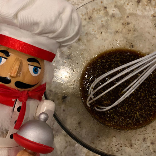 homemade balsamic vinaigrette in a glass bowl with a white silicone whisk that has a copper handle. There's a nutcracker that looks like a chef in the foreground on the left.