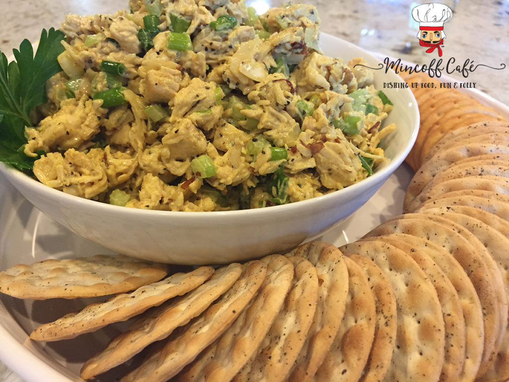 Beautiful Curry Chicken Salad in a white bowl, which inside another white dish that has round crackers circling the salad.