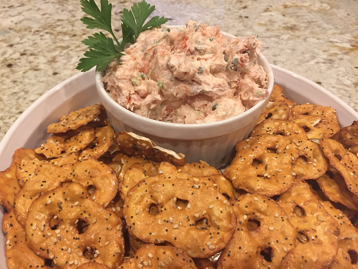 Smoked salmon dip in a white bowl, garnished with fresh parsley and inside another white bowl that has many pretzel crisps to spread it on.