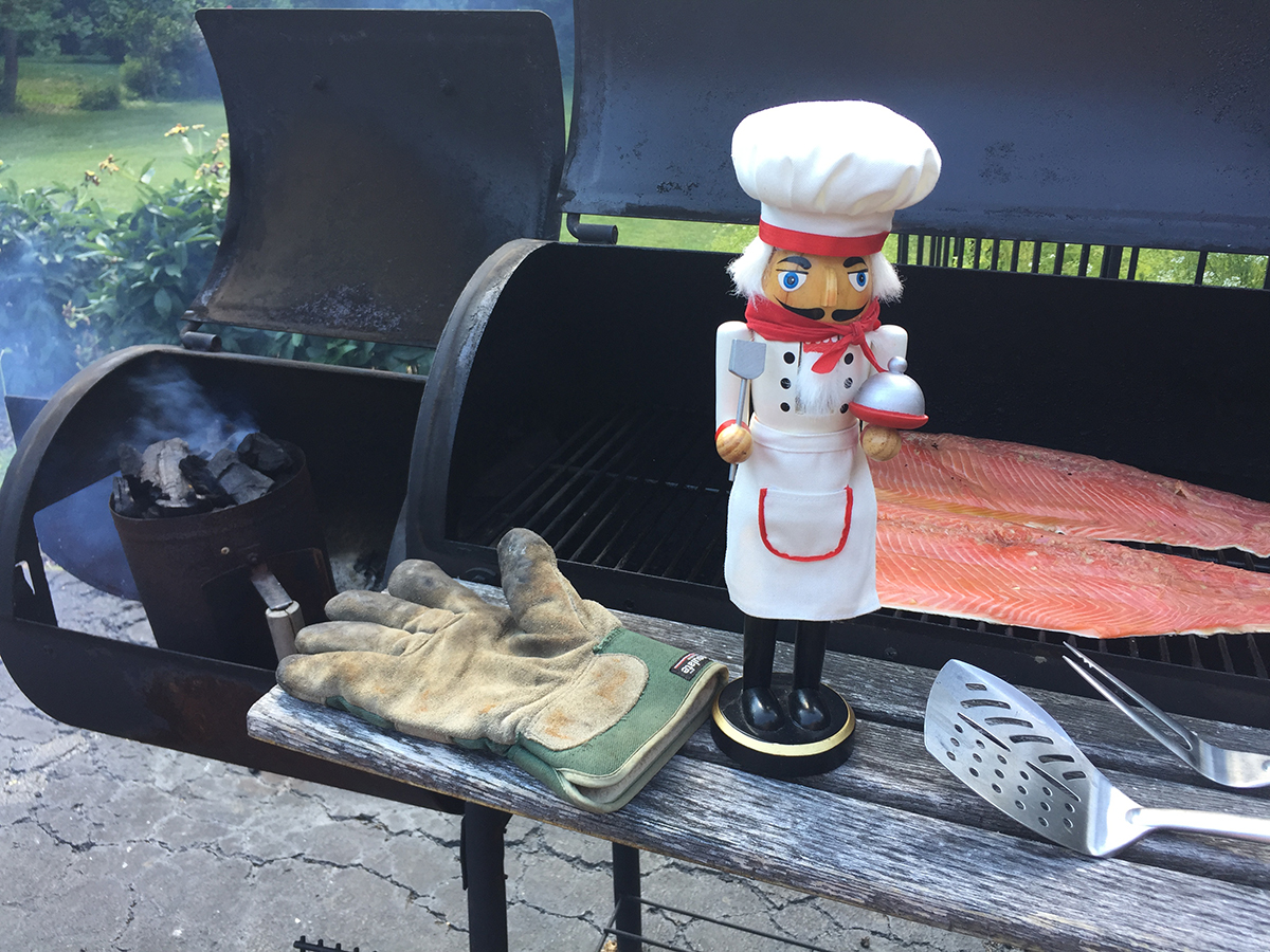 two salmon filets on the grill of a wood smoker ready to be smoked. There's a glove, grill tools and a nutcracker who looks like a chef sitting on the wood shelf in front of the smoker.