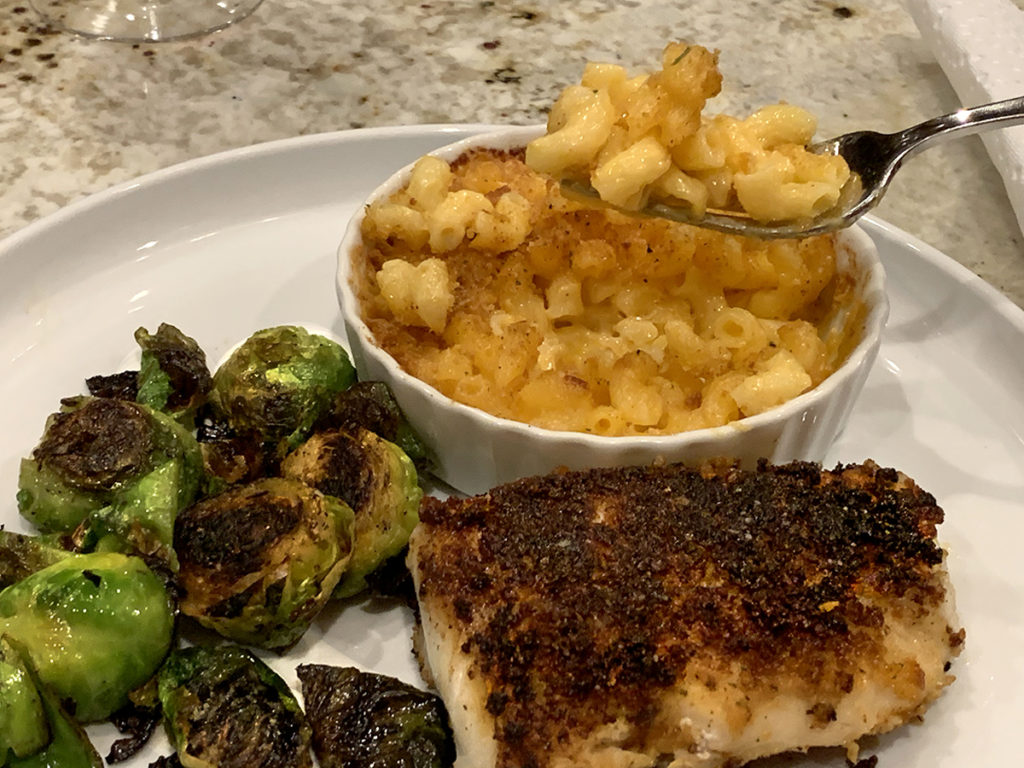 Pan seared brussels sprouts, breaded and pan fried cod and a small white ramekin with mac and cheese, all on round white plate.