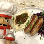 Bangers & Mash with Fried Reg Cabbage, sprinkled with parsley and a nutcracker that looks like a chef in the foreground.