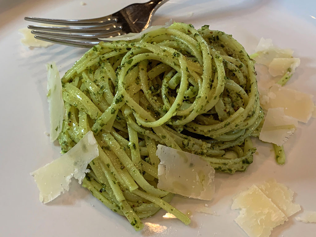 A swirled pile of linguini coated with green stinging nettle pesto sauce and a few shavings of parmesan cheese on a white plate with a fork.