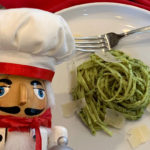 A swirled pile of linguini coated with green stinging nettle pesto sauce and a few shavings of parmesan cheese on a white plate with a fork. And a nutcracker who looks like a chef in the foreground.