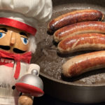 4 pork sausages or bangers in a skillet with a nutcracker that looks like a chef in the foreground.