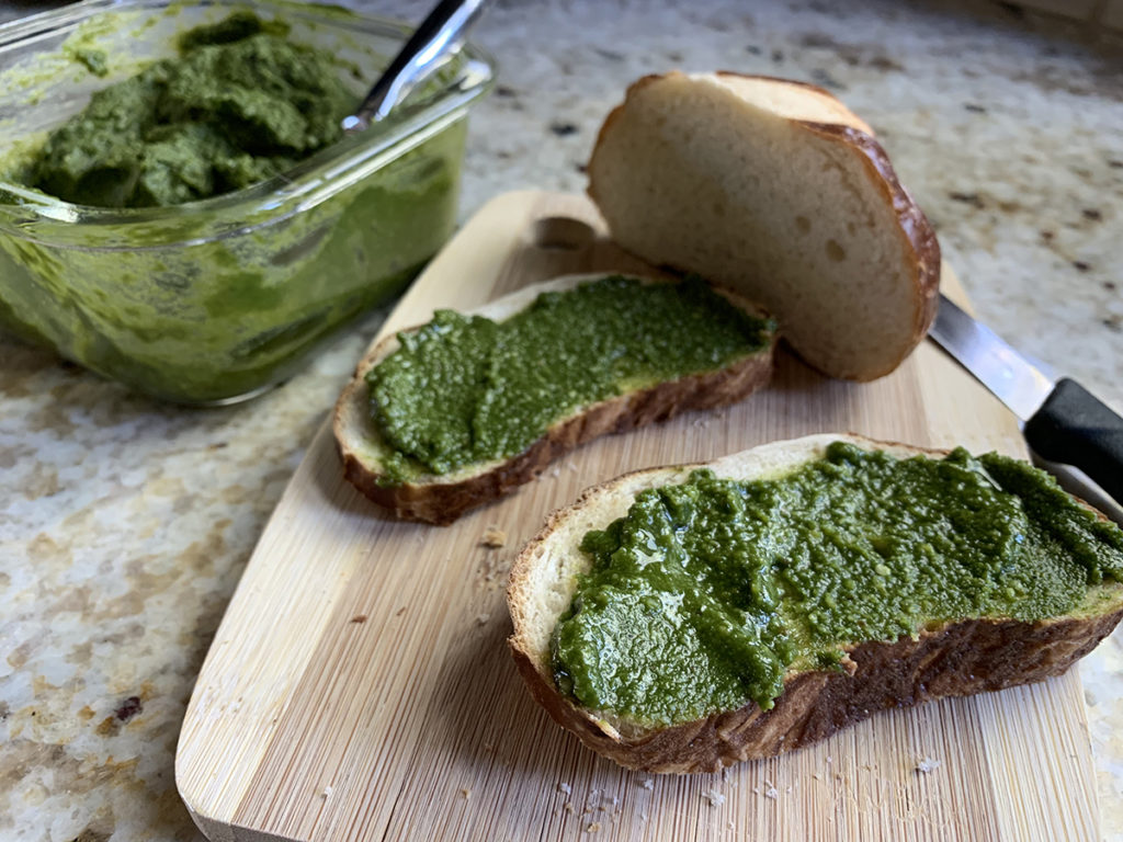 Stinging nettle pesto spread onto two small slices of pretzel bread, sitting on a small bamboo cutting board.