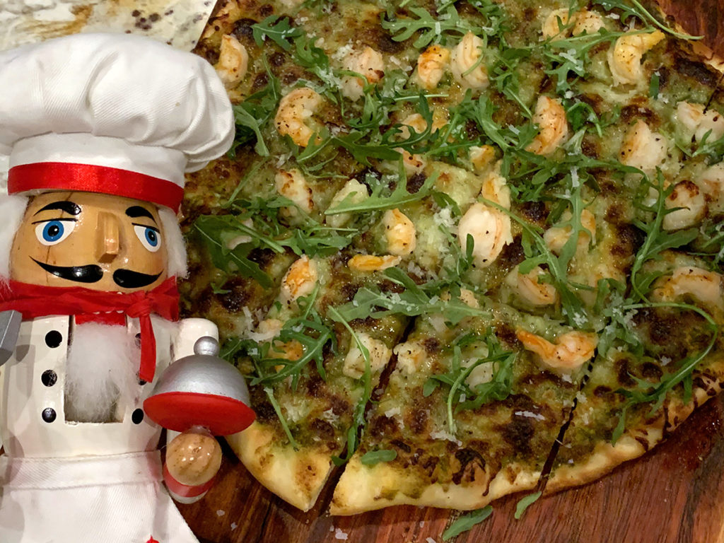 Baked shrimp & nettle pesto pizza topped with fresh arugula and parmesan cheese on a wood board. There's a nutcracker who looks like a chef in the foreground.