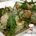 Two square slices of shrimp and nettle pesto pizza with arugala on a white plate with the minoff cafe logo in the bottom right corner.
