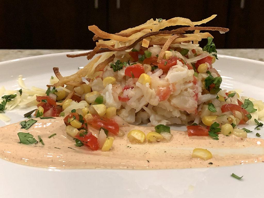 king crab, pico de gallo and chipotle cream sauce on a round white plate.