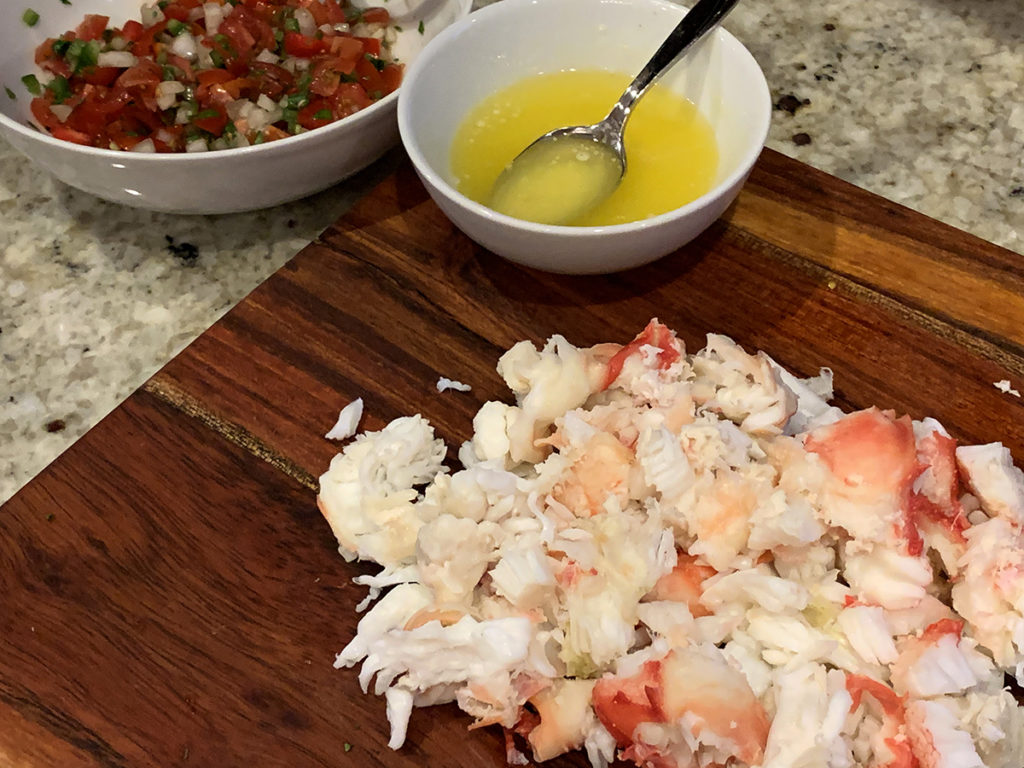 Alaskan King Crab with a small white bowl of melted butter on a wood cutting board.