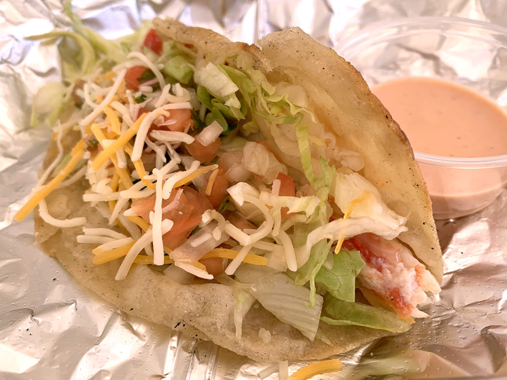 crab taco with pico de gallo, lettuce and shredded cheese in a flour tortilla .